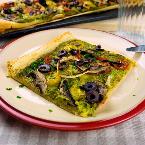 Spinach pesto tart with tomatoes, mushrooms and olives