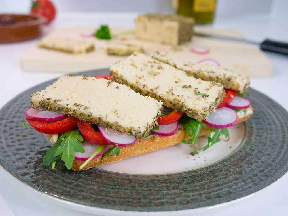 easy to make herb crusted cashew cheese on a sandwich