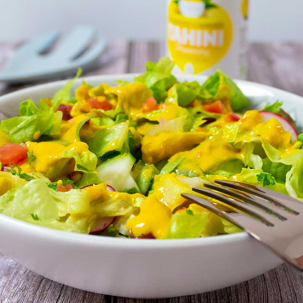 tahini dressing with turmeric and ginger on mixed salad