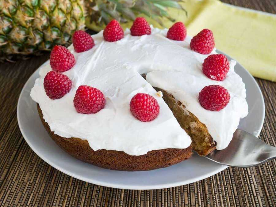 Easy pineapple cake with whipped coconut cream and topped with raspberries